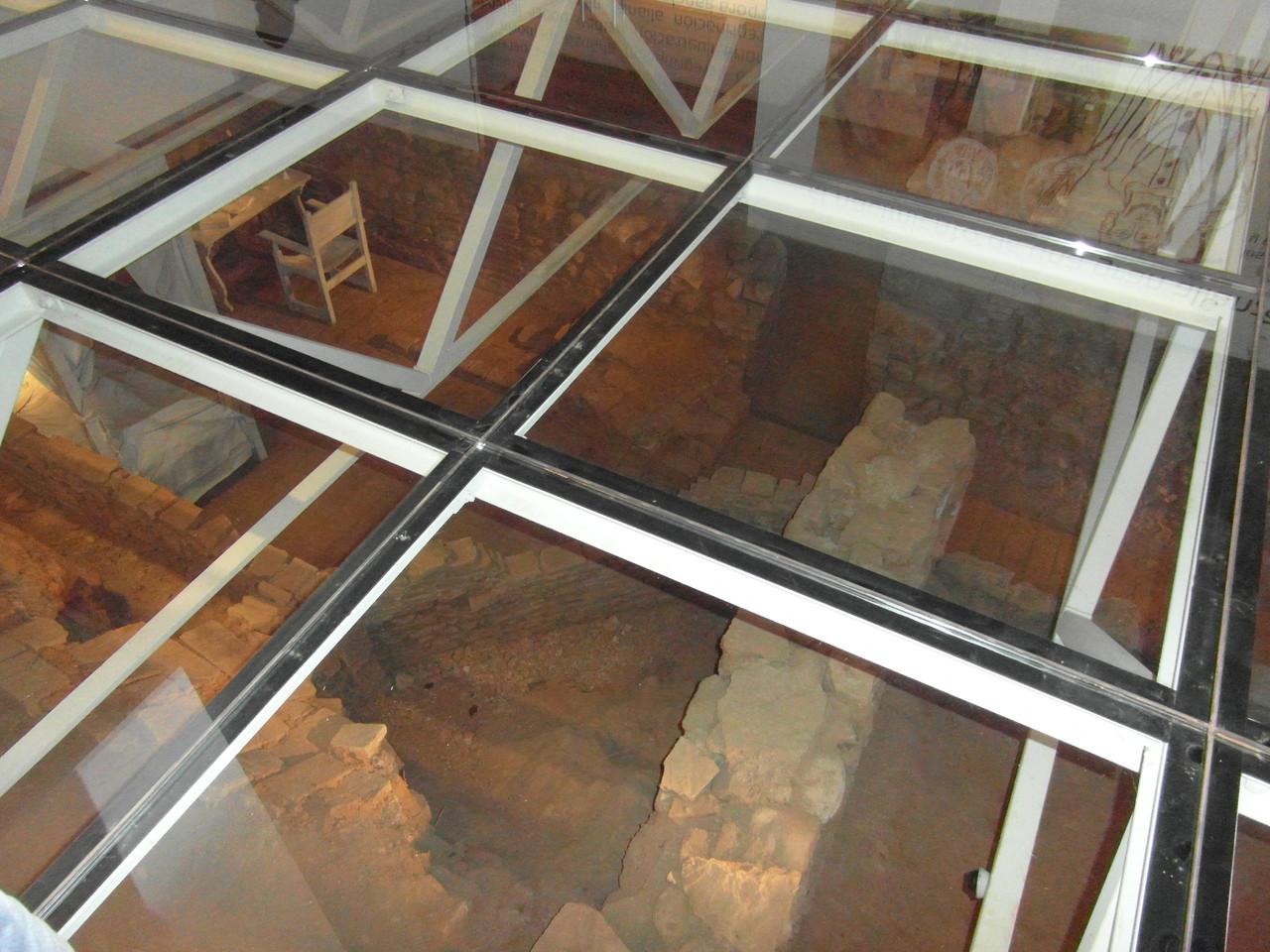 Vista detalle, se anda sobre los restos del monasterio, sobre cristal.